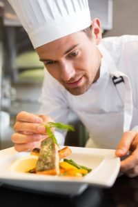 Concentrated male chef garnishing food in kitchen in essex
